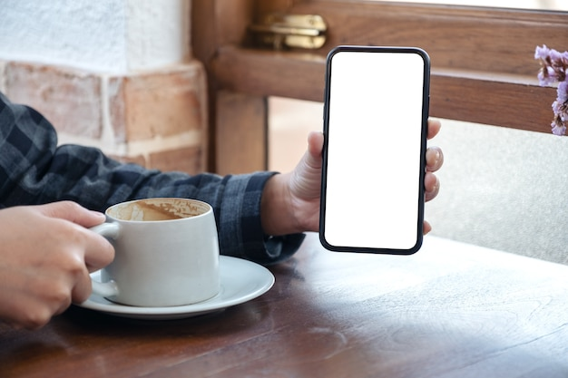 Woman holding and showing black mobile phone with blank white screen while drinking coffee