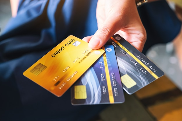A woman holding and showing credit card