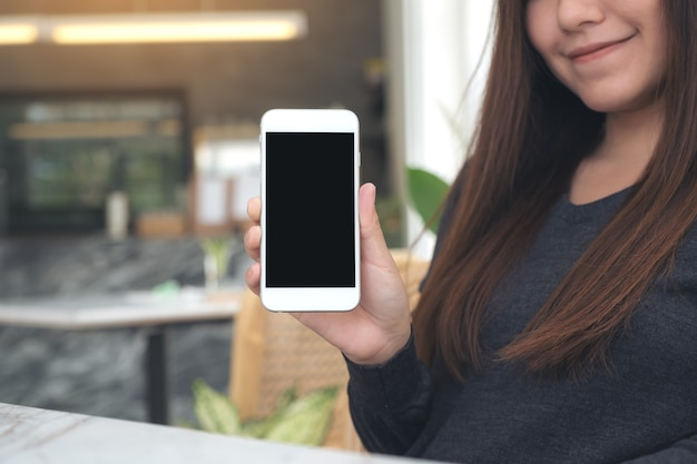 Woman holding and showing white mobile phone with blank black screen