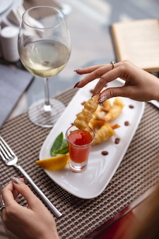 A woman holding shrimp with sweet chilli sauce slice of lemon and glass of white wine on the table