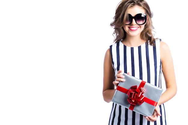Женщина, держащая серебряную подарочную коробку с красной лентой, изолированной на белом.