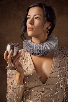 Woman holding silver wine glass with purple grapes
