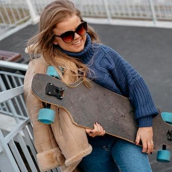 Donna che mantiene lo skateboard all'aperto