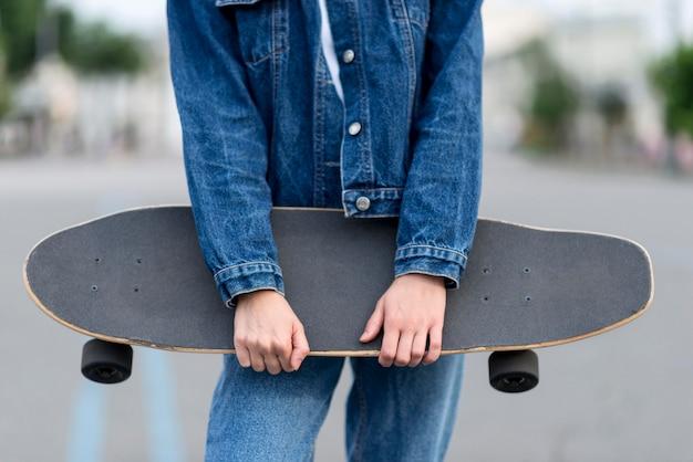Donna che tiene uno skateboard con le sue mani