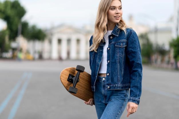 Donna che mantiene uno skateboard