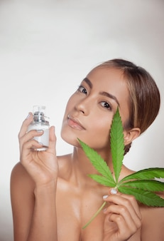 Woman holding a skin cream made from cannabis extract and marijuana leaf