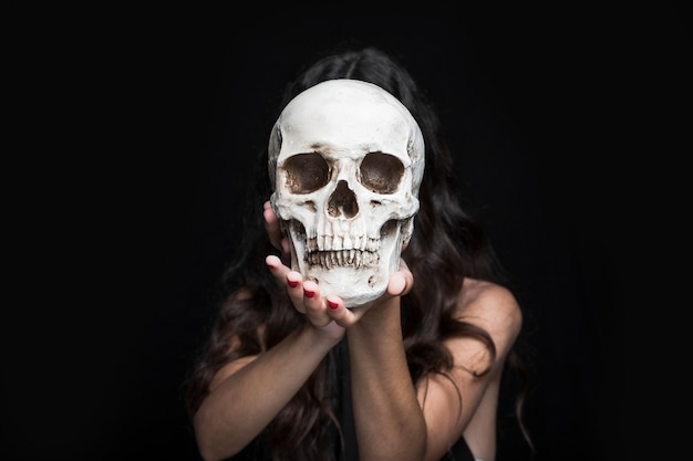 Woman holding skull before face