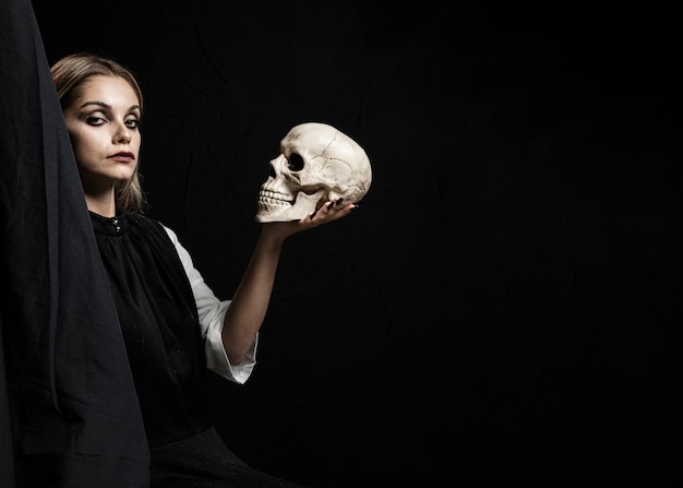 Woman holding skull with copy space