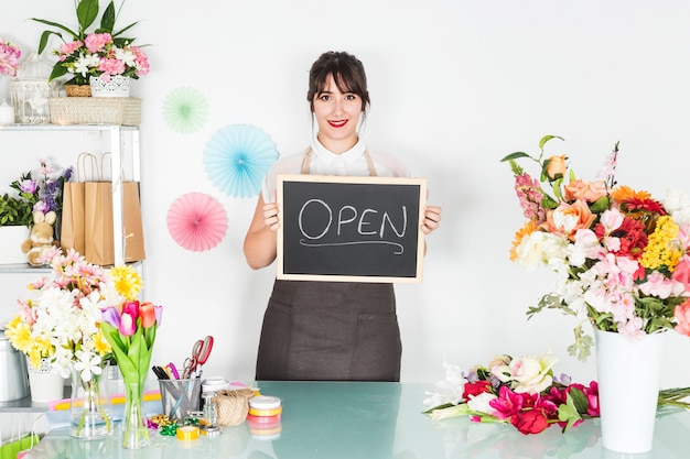 Woman holding slate with chalkdrawn open word in floral shop