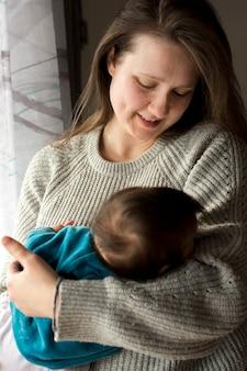 眠っている赤ちゃんを腕の中で保持している女性