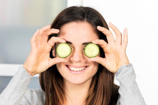 Donna che mantiene fetta di cetriolo sopra l'occhio