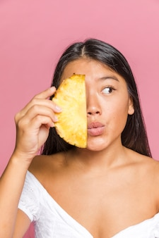 Woman holding a slice of pineapple and looking away