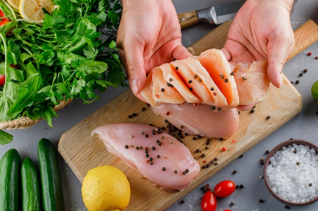 Woman holding sliced chicken breast with greens, cucumber, lemon, salt on a cutting board on gray surface, top view