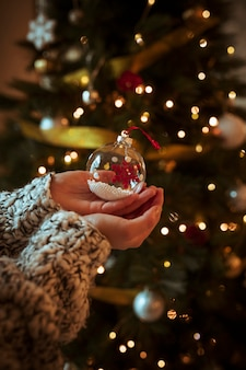 Woman holding small bauble in hand