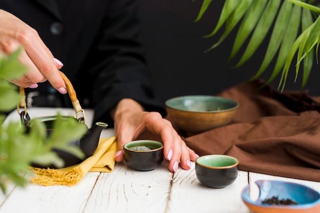 お茶と小さなカップを保持している女性