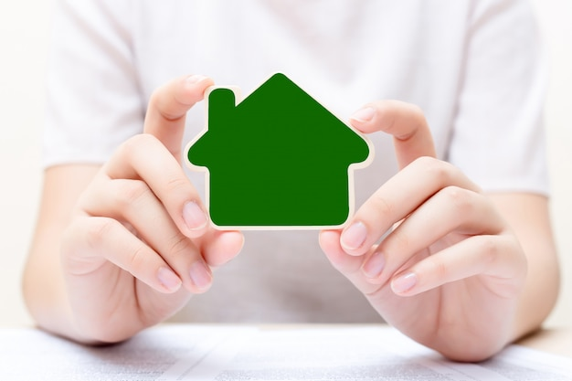 Woman holding the small home over the document
