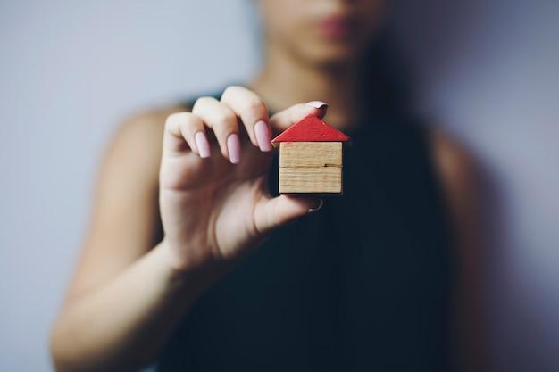 Женщина держит маленький дом