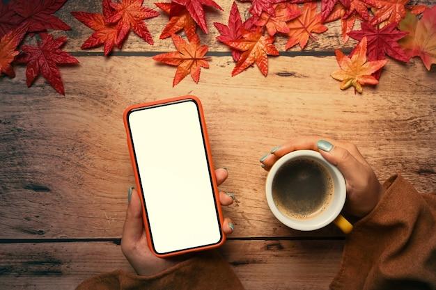 가을 단풍나무 잎이 달린 스마트 폰과 커피 컵 나무 테이블을 들고 있는 여자. 가을 시즌 컨셉입니다.