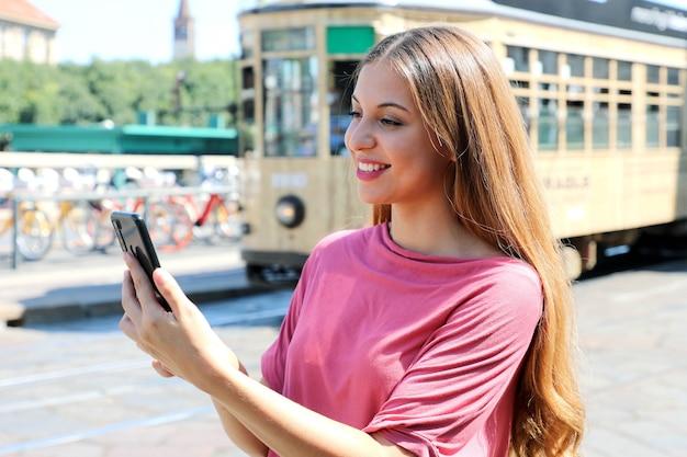 지나가는 오래 된 전차와 거리에서 그녀의 손에 스마트 폰을 들고 여자