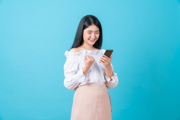 拳の手でスマートフォンを持ち、成功に興奮している女性。