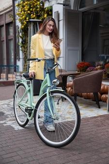 Женщина, держащая смартфон и велосипед в городе