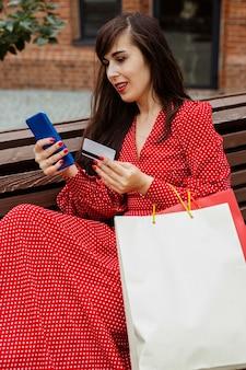 販売中にオンラインで購入するスマートフォンとクレジットカードを保持している女性