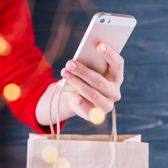 Woman holding smartphone and gift bag