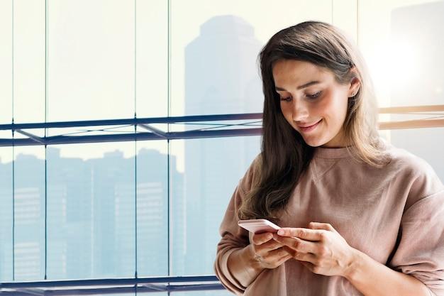 도시 전망 리믹스 미디어를 사용하여 새로운 표준에서 스마트폰 배경을 들고 있는 여성