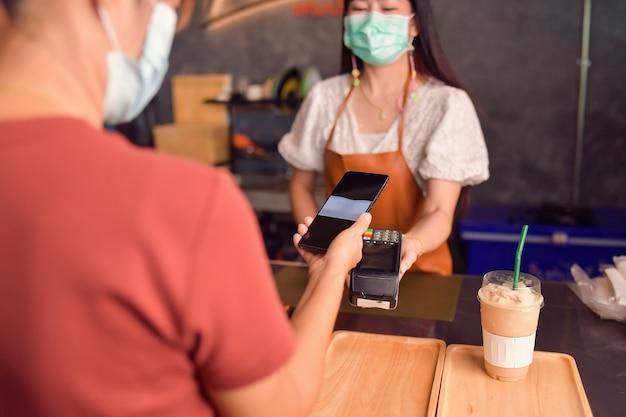電子決済機の近くにスマートフォンを持っている女性