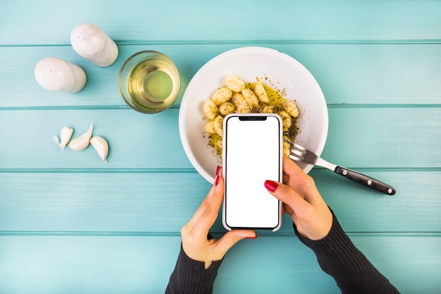 Woman holding smartphone over gnocchi pasta