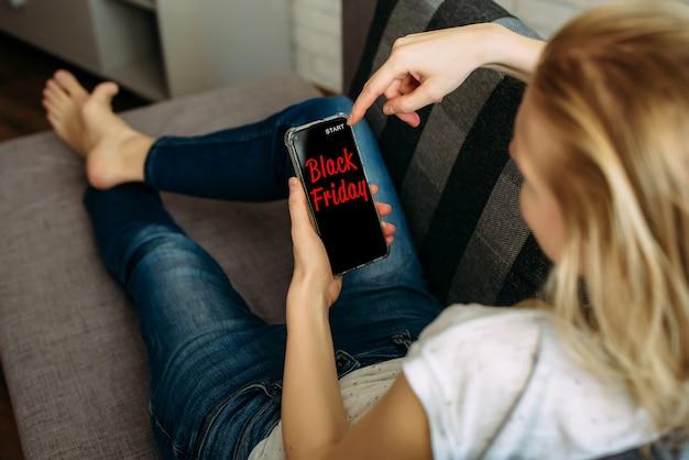 Женщина, держащая смартфон в руке, лежа на диване. безопасность покупок из дома во время карантина.