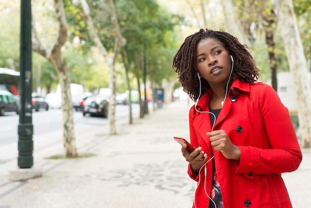 Woman holding smartphone and looking side on street