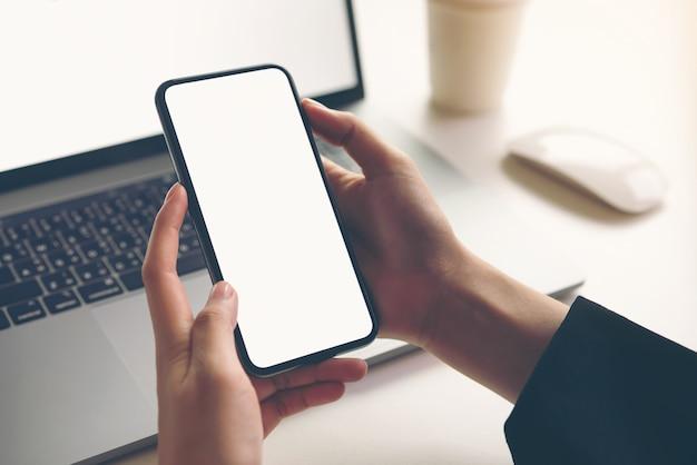 空白の画面とテーブルの上のノートパソコンのスマートフォンモックアップを保持している女性。