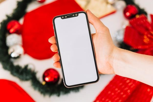 Woman holding smartphone near christmas tree decoration