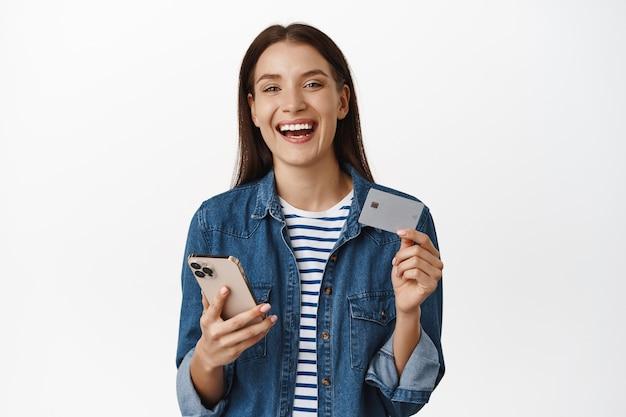 Женщина держит смартфон, показывает кредитную карту, удовлетворенно улыбается и смеется, покупая что-л. на мобильном телефоне на белом