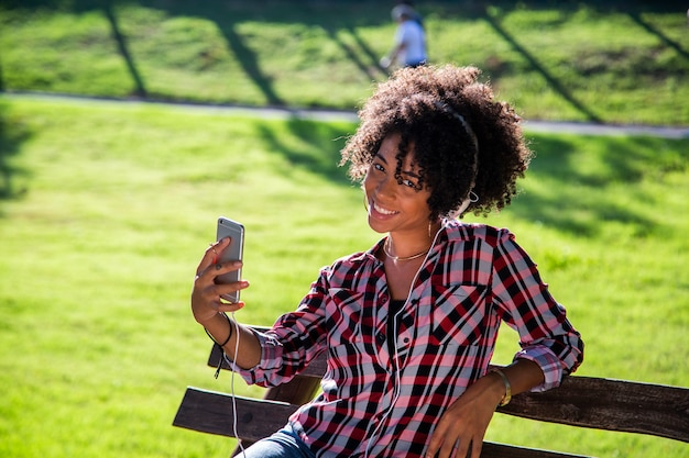 Woman holding smartphone taking selfie photo and standing in park