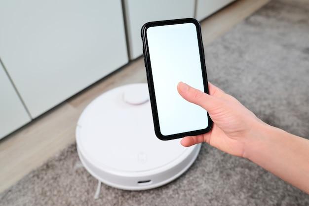 청소 시작을 위해 로봇 진공 청소기를 제어하기 위해 모바일 응용 프로그램을 사용하는 스마트 폰을 들고 여자. 스마트 라이프 기술 개념 아이디어.