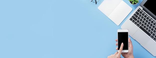 최소한의 파란색 책상, 온라인 쇼핑, 인터넷 결제, 전자 상거래의 개념으로 스마트 폰을 들고 여자