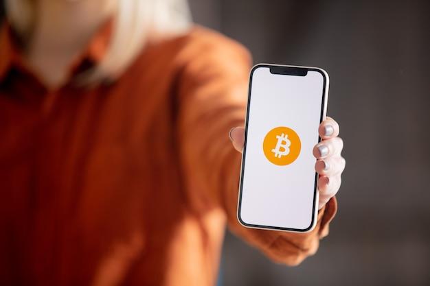 画面にビットコインのロゴが付いたスマートフォンを持っている女性