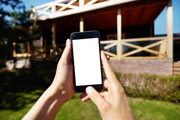 Женщина, держащая смартфон с пустым белым экраном