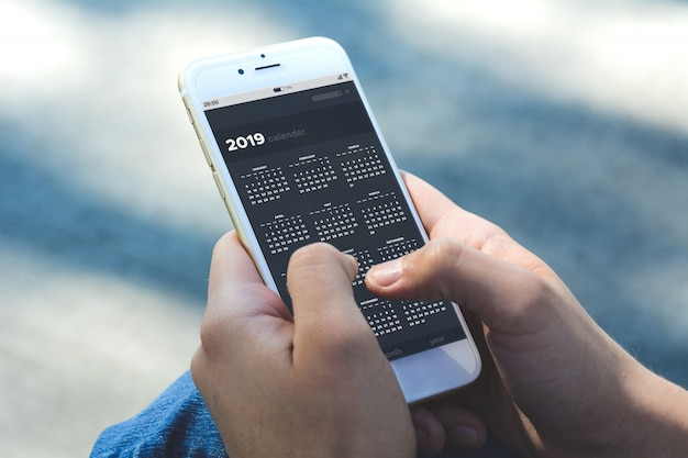 Woman holding smartphone with calendar app