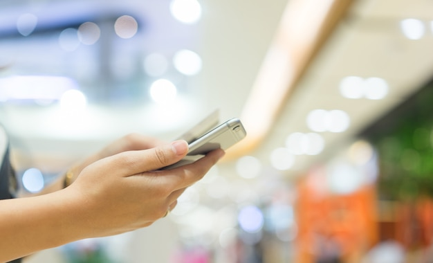 Woman holding smartphone with credit card for pay online shopping