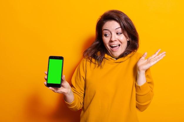 녹색 화면이 있는 스마트폰을 들고 있는 여성
