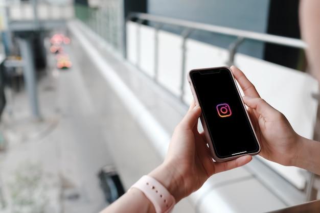 画面上のソーシャルメディアとスマートフォンを保持している女性