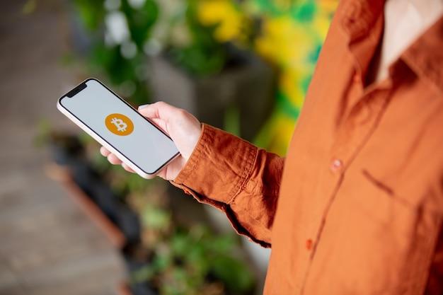 自宅の画面にビットコインのロゴが付いたスマートフォンを持っている女性