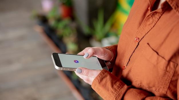 집에서 화면에 페이스 북 메신저 로고와 함께 스마트 폰을 들고 여자
