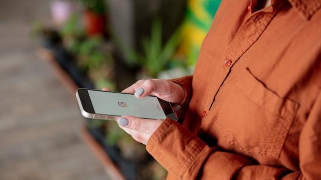 自宅の画面にinstagramのロゴが付いたスマートフォンを持っている女性