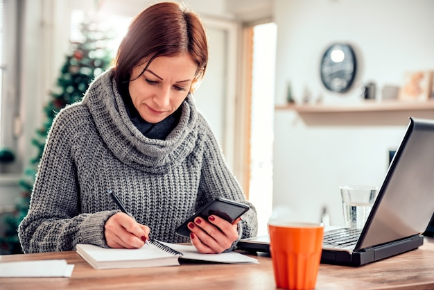 Woman holding smartphone and writing down notes in her notebook