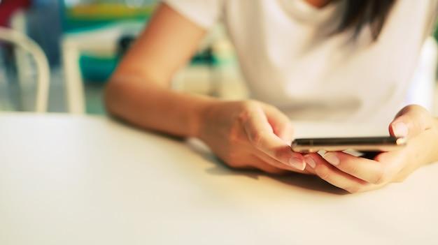 スマートフォンで動作するモバイルデバイスを持っている女性。携帯電話技術のeコマースの概念。