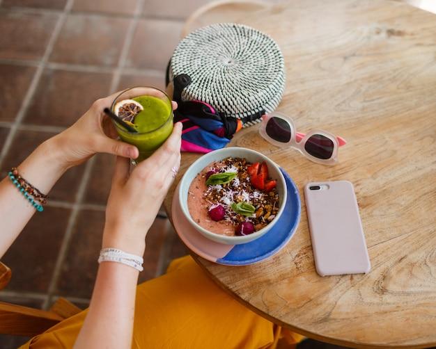 Женщина, держащая пюре. чаша суперпродуктов с чиа, мюсли и авокадо.
